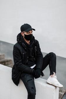 Elegante bel giovane modello maschile con maschera protettiva e berretto in una giacca alla moda e una felpa con cappuccio con scarpe da ginnastica si siede per strada vicino a un muro bianco