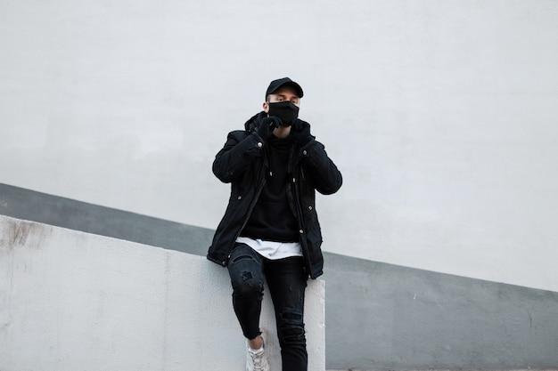Modello elegante e bello con una maschera protettiva e un berretto nero con una giacca e una felpa con cappuccio vicino al muro della strada e stile urbano maschile e pandemia