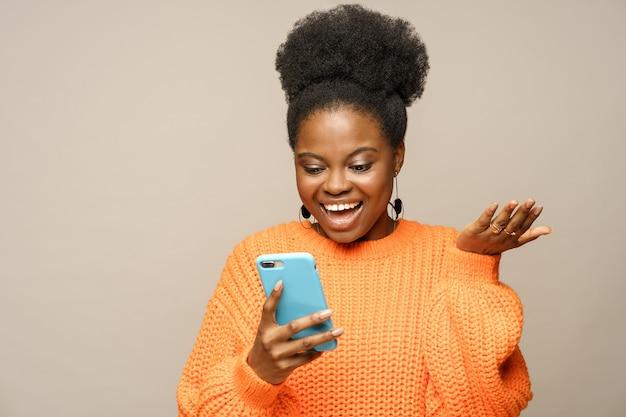 Elegante donna afro felice indossa un maglione arancione, ride, legge il messaggio, chiacchiera sui social media