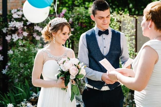 Elegante sposa felice con bouquet di peonie con corona, sposo tenere in mano certificato di matrimonio