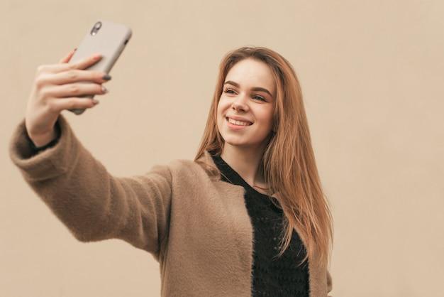 Elegante ragazza felice indossa un cappotto, si erge sullo sfondo di una parete beige e fa una foto su uno smartphone, selfie