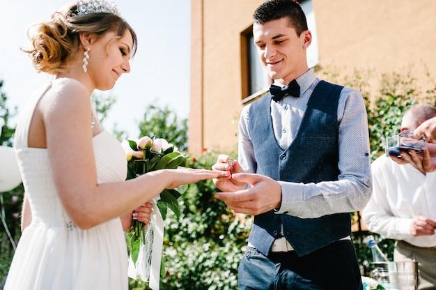 Lo sposo felice alla moda indossa l'anello d'oro sul dito della sposa.