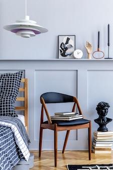 Elegante camera da letto hipster con sedia di design, cornici per poster, libri, orologi, decorazioni, tappeti, bellissime lenzuola, coperte e cuscini in un arredamento moderno.