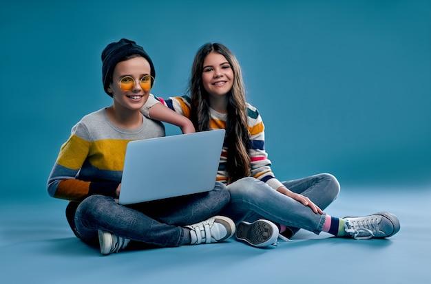 Un ragazzo alla moda hipster con cappello e occhiali e una ragazza carina siedono a gambe incrociate e studiano o giocano su un laptop isolato su un blu.