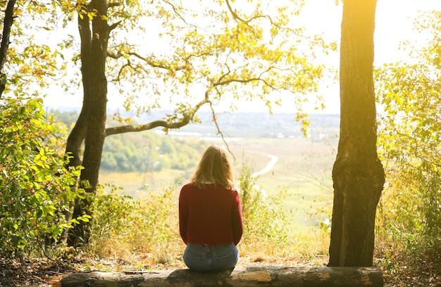 La ragazza alla moda dei pantaloni a vita bassa sta sedendosi nella foresta. donna felice che gode della natura autunnale. bel paesaggio. concetto di viaggio di stile di vita. maglione rosso scuro. foglie gialle sugli alberi. vista dalla collina di montagna.