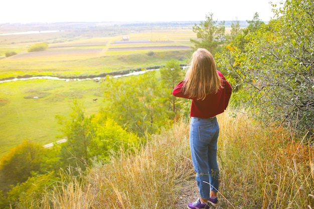 Ragazza alla moda hipster in piedi sulla collina di montagna. donna felice che gode della natura autunnale. bel paesaggio. concetto di viaggio di stile di vita. maglione rosso scuro. foglie gialle sugli alberi.