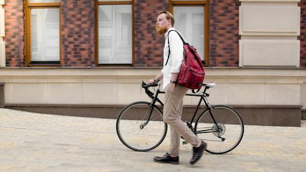 Uomo alla moda hipster con barba che cammina con la bicicletta sulla strada della città.