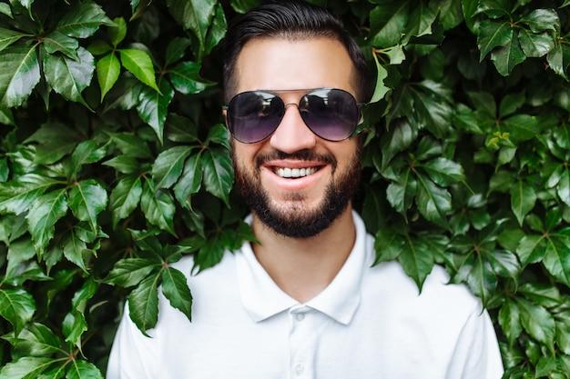 Pantaloni a vita bassa alla moda con barba e maglietta bianca sulla parete di parete verdeggiante