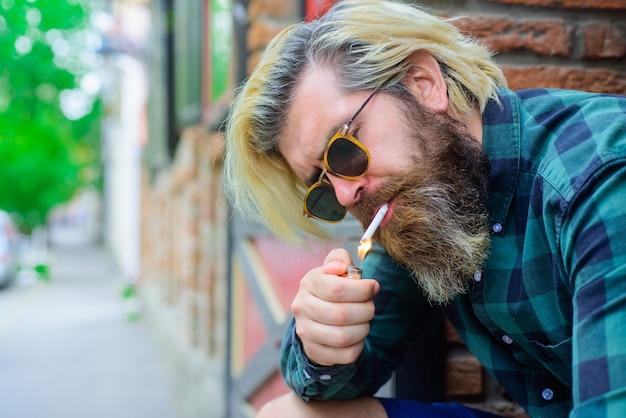 Elegante hipster con sigaretta fumo di sigaretta uomo sensuale che fuma fuori tabacco hipster