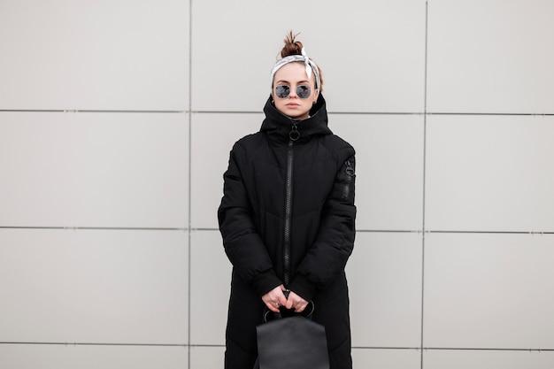 Giovane donna alla moda hipster in occhiali da sole alla moda in una bandana in una giacca lunga alla moda con uno zaino alla moda in pelle vicino a un muro bianco. ragazza moderna americana. moda femminile.