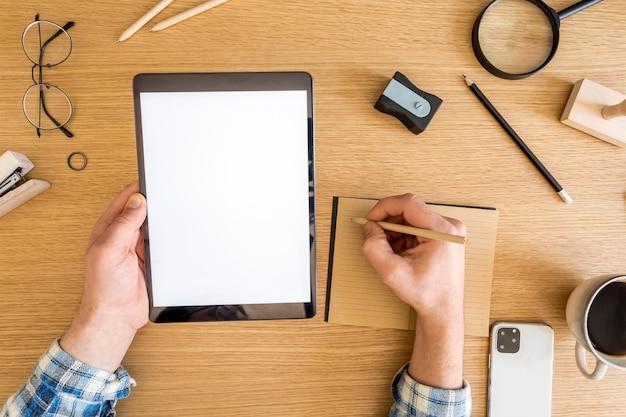 Elegante composizione per l'home office di schermo tablet mock up, forniture per ufficio, tazza di caffè, telefono, macchina fotografica, piante e accessori personali nel concetto di business.