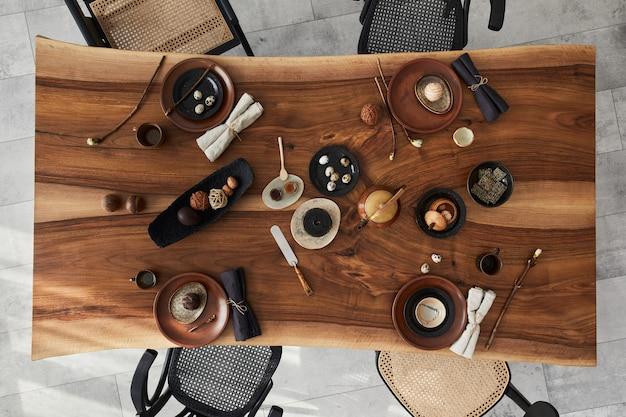 Elegante design degli interni della sala da pranzo con tavolo in legno di noce, sedie retrò, stoviglie, piatti, tovaglia, teiera, cibo, decorazioni e accessori eleganti. pavimento in cemento.. vista dall'alto.