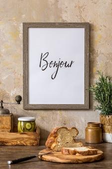 Interni eleganti dello spazio cucina con tavolo in legno, cornice per foto marrone mock up, pane, tazza di tè, erbe aromatiche, verdure e accessori da cucina nel concetto wabi sabi di arredamento per la casa.