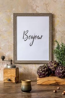 Interni eleganti dello spazio cucina con tavolo in legno, portafoto marrone, erbe aromatiche, verdure, teiera, tazze e accessori da cucina nel concetto di arredamento per la casa wabi sabi.