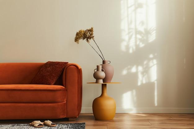 Interni eleganti del soggiorno in una casa elegante con divano di design, tavolino giallo, fiori secchi, cuscino, arredamento per tappeti e accessori personali in un arredamento moderno. copia spazio.