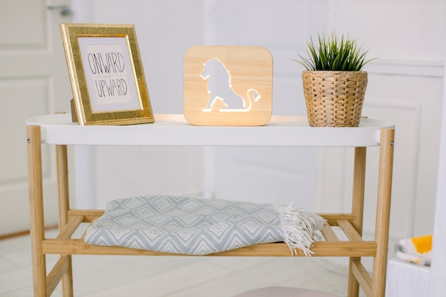 Interni eleganti del soggiorno. home decor. tavolino con portafoto, lampada decorativa in legno con immagine di leone e pianta artificiale in vaso di fiori di vimini.