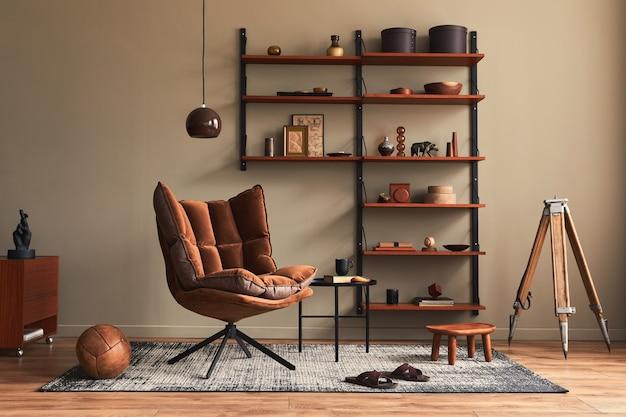 Interni eleganti del soggiorno con poltrona di design marrone, libreria in legno, lampada a sospensione, arredamento in moquette, cornici ed eleganti accessori personali in un moderno arredamento retrò.