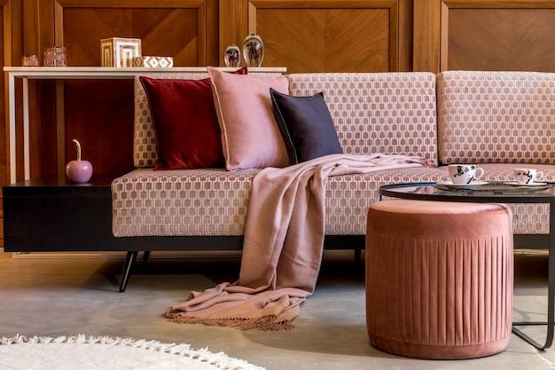 Interni eleganti del soggiorno con divano design in velluto rosa, elegante pouf, tavolino da caffè, pianta, cuscini, decorazioni ed eleganti accessori personali. decorazioni per la casa moderne e home staging.