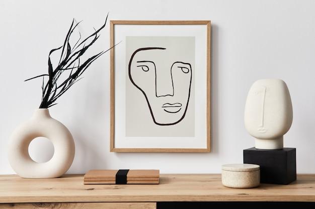 Interni eleganti del soggiorno con cornice, comò in legno, libro, foglia nera in vaso di ceramica ed eleganti accessori personali. concetto minimalista di arredamento..
