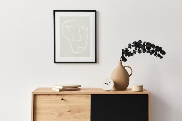 Interni eleganti del soggiorno con cornice, comò in legno, libro, foglia di eucalipto in vaso di ceramica ed eleganti accessori personali. concetto minimalista di arredamento per la casa.