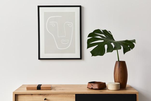 Interni eleganti del soggiorno con cornice, comò in legno, libro, foglia tropicale in vaso di ceramica ed eleganti accessori personali. concetto minimalista di arredamento per la casa.