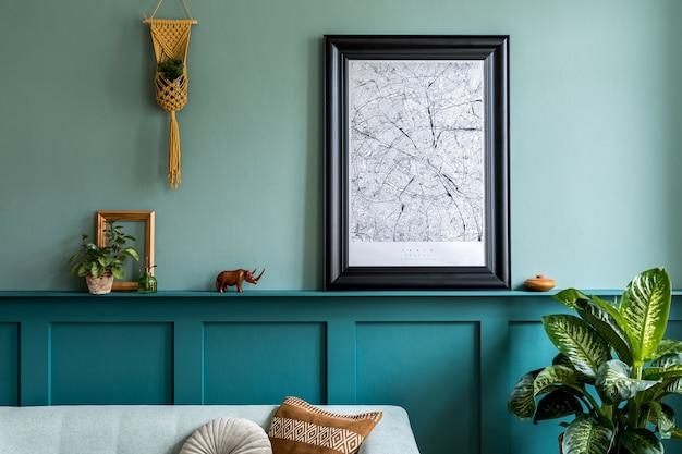 Interni eleganti del soggiorno con cornice per poster, divano alla menta, mobili, piante, decorazioni e accessori personali eleganti. boiserie verde con ripiano. arredamento moderno per la casa. .