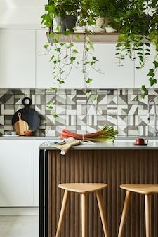 Elegante design degli interni della cucina con sala da pranzo. area di lavoro con accessori da cucina in background. pareti creative con pannelli in legno. stile minimalista e concetto di amore per le piante.