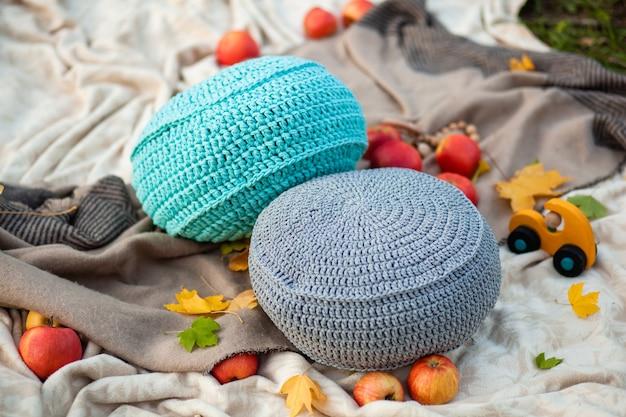 Elegante pouf beige lavorato a maglia in interni moderni, pouf accanto a una poltrona con un giocattolo per bambini