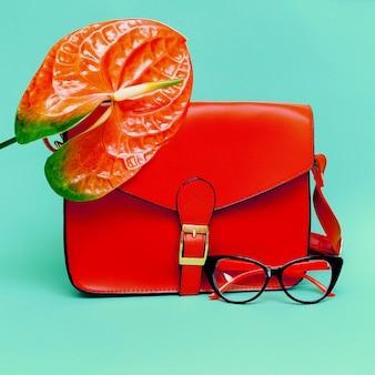 Eleganti occhiali da sole e borsetta da donna. concentrati sul rosso.