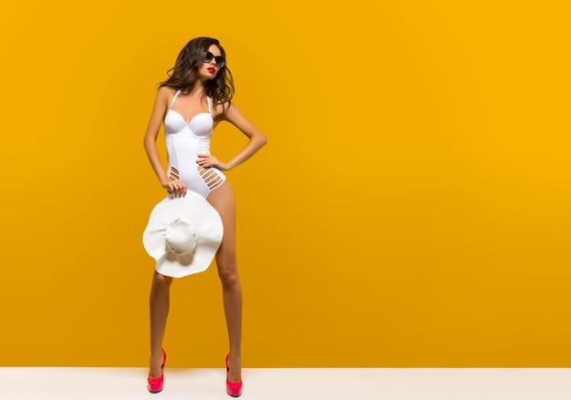 Elegante signora che indossa un bikini, in occhiali da sole e cappello bianco
