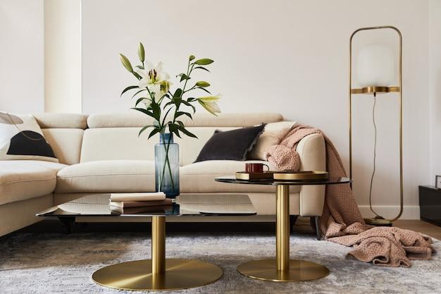 Elegante composizione interna del soggiorno con divano beige, tavolino da caffè in vetro, moquette sul pavimento e accessori glamour. modello.