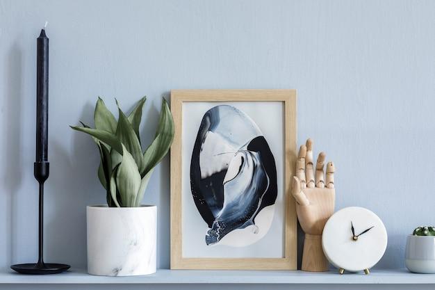 Interni eleganti del soggiorno in un elegante appartamento con cornice finta, orologio bianco, candela, pannelli in legno grigio e accessori eleganti sullo scaffale in un moderno home staging.