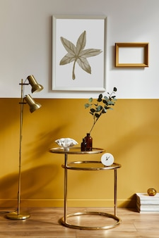 Elegante soggiorno in interni moderni con tavolino design oro, cornici per poster finti, fiori in vaso, decorazione, lampada, libro e accessori personali nell'arredamento della casa. modello.
