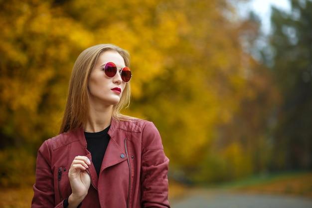 Elegante donna bionda dai capelli lunghi che indossa giacca di pelle e occhiali rossi. spazio vuoto