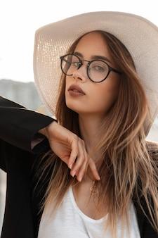 Elegante modello di giovane donna adorabile in occhiali alla moda in cappello di paglia alla moda in blazer nero alla moda posa per strada. ritratto fresco bella ragazza in voga bei vestiti all'aperto in città.