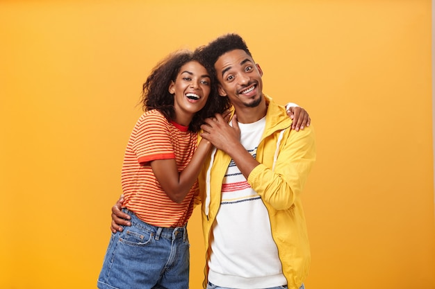 Coppie afroamericane alla moda e amorevoli che abbracciano e che sorridono ampiamente.