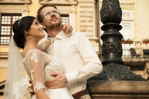 Elegante sposa di lusso e sposo elegante, abbracciati con tenerezza, sullo sfondo della città vecchia di lviv