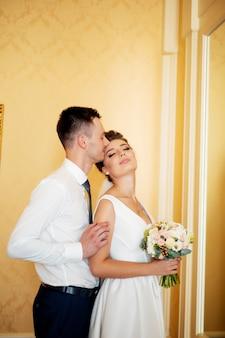 Tenersi per mano di lusso alla moda della sposa e sposo elegante bello