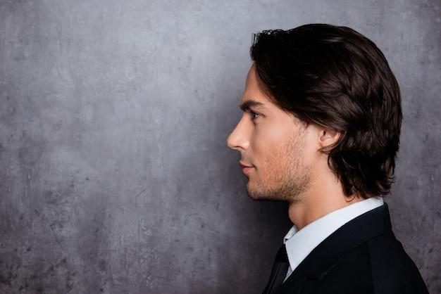 Uomo alla moda in abiti da cerimonia con barba incolta e bei capelli, foto vista laterale