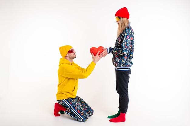 Uomo alla moda che regala un cuore alla ragazza in abiti colorati sul muro bianco
