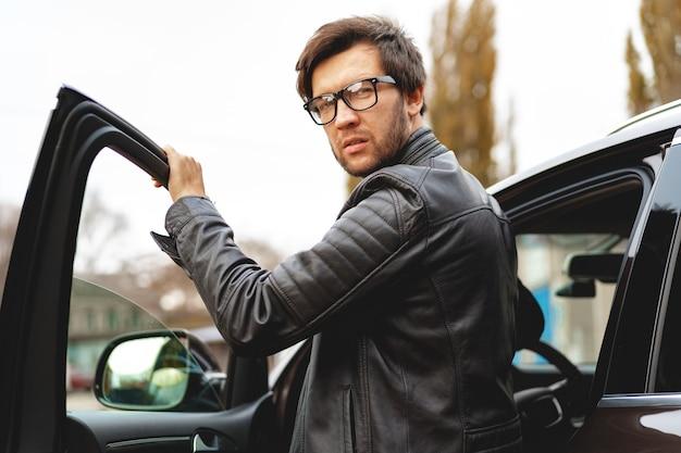 Uomo alla moda con gli occhiali si siede in un ritratto di auto