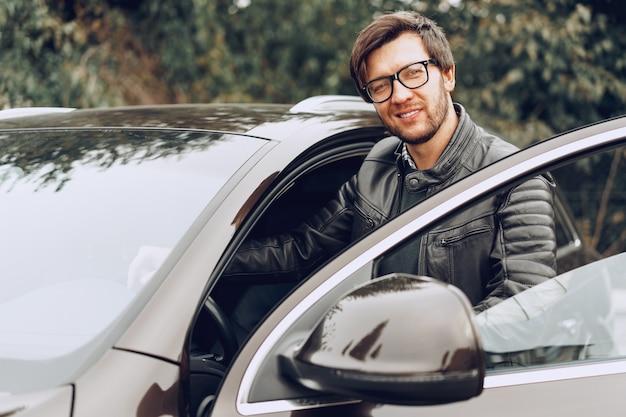 Uomo alla moda con gli occhiali si siede in una macchina