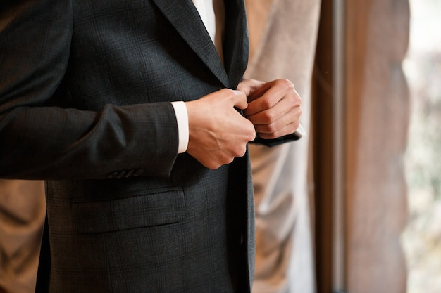 Uomo alla moda sposo che si abbottona un bottone sulla giacca