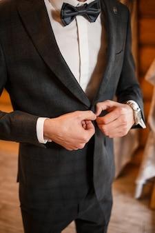 Sposo uomo alla moda che si abbottona un bottone sulla giacca