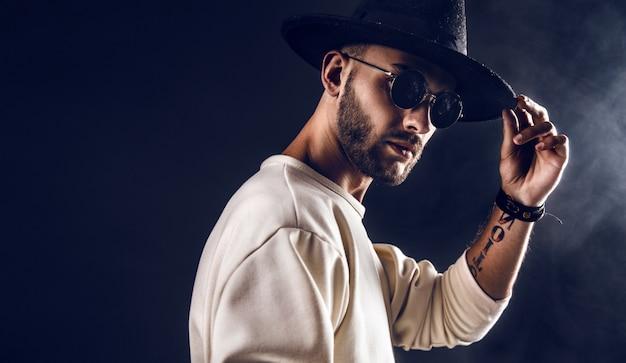 Uomo alla moda in cappello e occhiali da sole