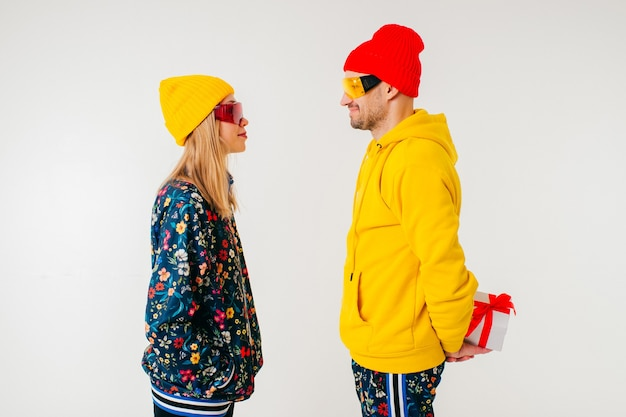 Uomo alla moda che nasconde un regalo da una ragazza in abiti colorati su sfondo bianco