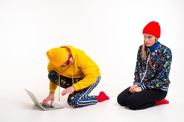 Uomo alla moda che nasconde lo schermo del laptop da donna in abiti colorati sul muro bianco