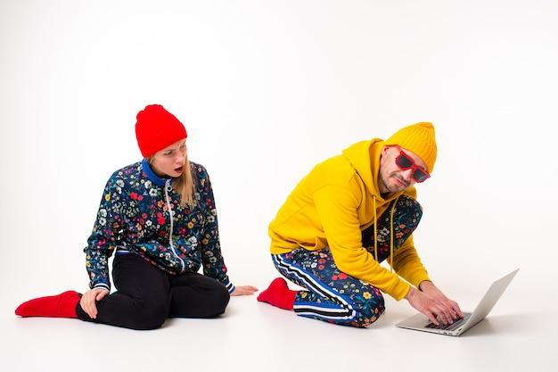 Uomo alla moda che nasconde lo schermo del laptop da donna in abiti colorati