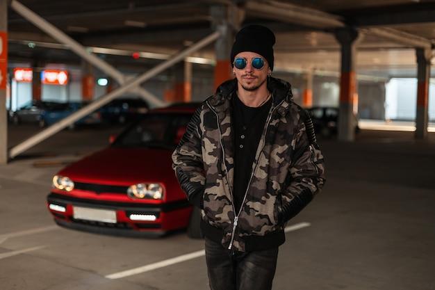 Elegante uomo hipster con occhiali da sole e cappello nero con giacca invernale militare di moda cammina per strada vicino a un'auto rossa al parcheggio