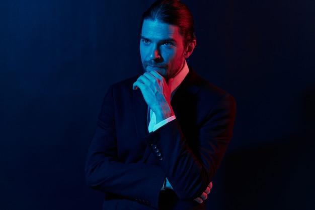 Uomo alla moda in una giacca in posa di fiducia in se stessi sfondo scuro